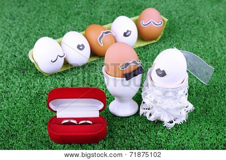 Egg bride and bridegroom with guests on green background