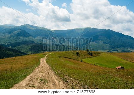 Dirt Road Against The Landscape In The Ukrainian Carpathians