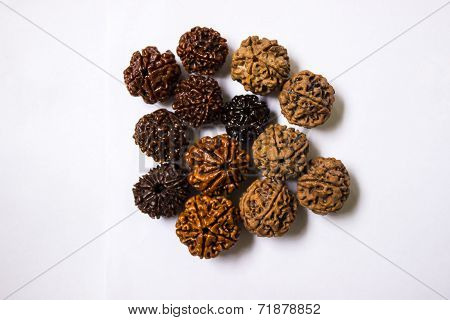 Rudraksha beads of varied faces, colours, shapes and sizes on an isolated background