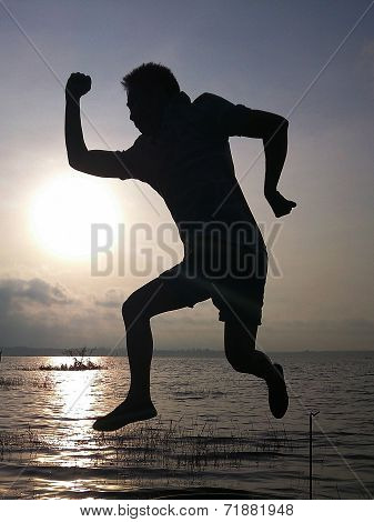 Silhouette Of Young Man Jumping.