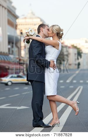 Couple in a kiss on the road. Wedding theme.