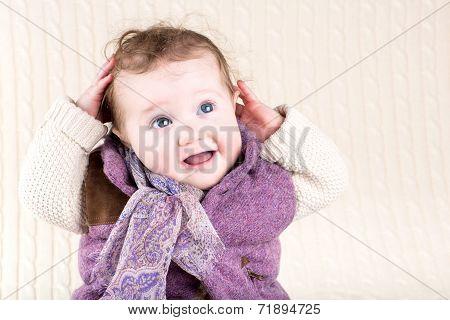 Beautiful Little Girl In A Warm Purple Jacket Sitting On A Knitted Blanket