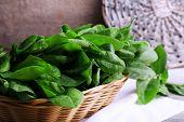 stock photo of sorrel  - Fresh sorrel in round wicker basket on napkin on wooden background - JPG