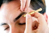 picture of eyebrow  - Portrait of man removing eyebrow hairs with tweezing - JPG