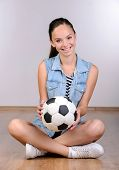 picture of physical education  - Cheerful teenage girl soccer player sitting on floor relaxing holding football - JPG