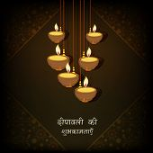 picture of diwali lamp  - Beautiful illuminated hanging oil lit lamps on floral design decorated brown background with wishes in Hindi text for Diwali festival celebrations - JPG