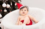 picture of santa baby  - Cute baby girl with santa hat sitting in front of a Christmas tree - JPG