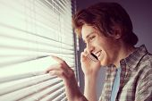 stock photo of blind man  - Young man smiling and talking on the phone in front of a window - JPG