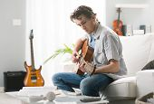 picture of compose  - Young man playing guitar and composing a song sitting on sofa - JPG