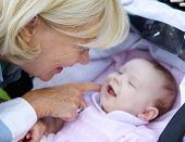 stock photo of tickle  - Portrait of a smiling grandmother tickling baby in pram