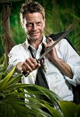 stock photo of machete  - Attractive confident businessman with machete walking in the jungle.