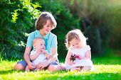 foto of three sisters  - Three happy kids brothers and sister laughing teenager boy little baby and a funny curly girl playing together with flowers in a sunny garden of their backyard on a warm sunny day - JPG