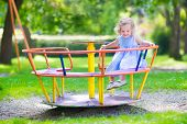 picture of little young child children girl toddler  - Happy laughing child beautiful little toddler girl with culy hair wearing a blue dress having fun on a playground enjoying a swing ride on a hot summer day in a sunny city park - JPG
