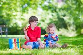 stock photo of school lunch  - Two laughing kids happy being back to school sitting outside a green sunny school yard reading books and enjoying healthy snack for lunch sandwich and fruit apple - JPG