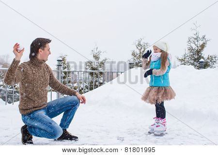 Happy family playing snowballs in winter snowy day