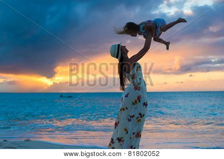 Young mom and little girl during summer vacation at sunset