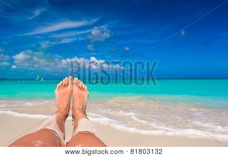 Female feet on white sandy beach