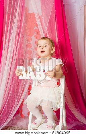 Little girl with a word baby in tutu skirt