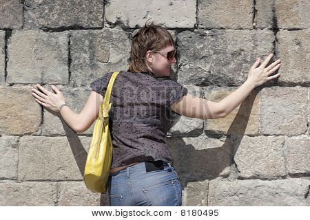 Smiling Girl Poses On Wall Background