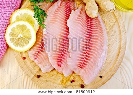 Tilapia with parsley and lemon on light board