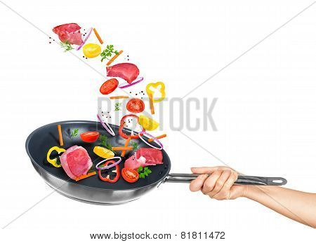 Meat And Mix Vegetables Fall Into Frying Pan On A White Background