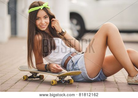 Young beautiful woman with the Board for skateboarding the city square.