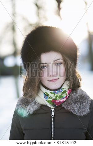 Mildly Smiling Woman With A Mild Sunshine Behind Her