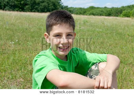 Smiling Boy In Green Outdoors