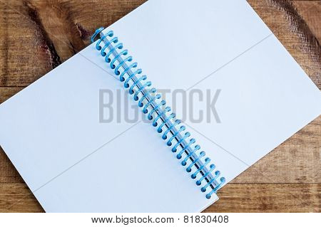 Open Notepad With Empty Pages Laying On A Wooden Table