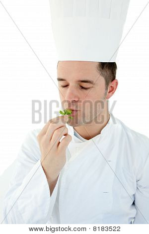 Young Cook With Closed Eyes Tasting A Herb Against White Background