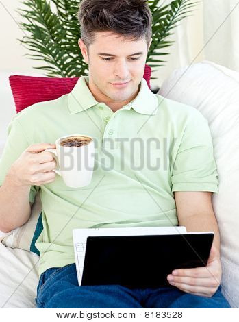 Smiling Young Man Holding A Cup Of Coffee Looking At A Laptop