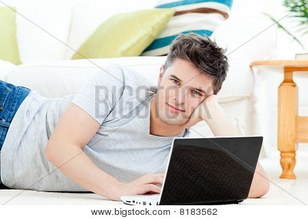 Handsome Young Man Lying On The Floor With A Laptop