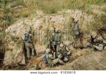 Group Of Soldiers Hiding In The Trenches And Firing