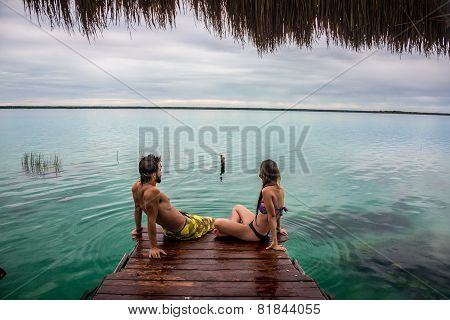 Beautiful Couple In Love Looking At Tranquil Bacalar Lake. Riviera Maya, Mexico. Tropical Travel.