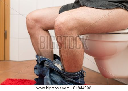 Closeup Man Sitting On A Toilet Bowl