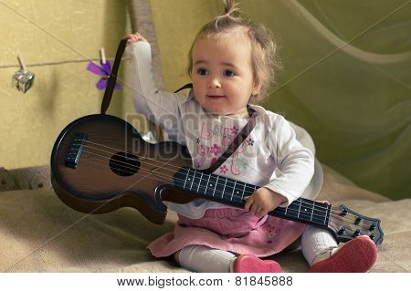 Smiling Girl With Guitar On The Bed