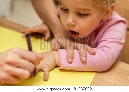 Mother And Child Are Painting The Hand Outline