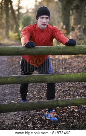 Man Stretching On Run Through Winter Woodland