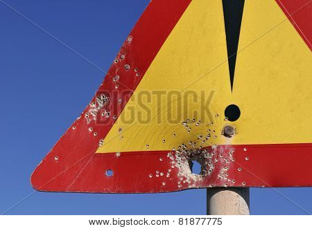 caution road sign with holes