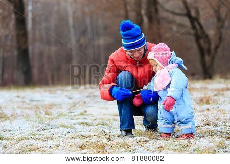 father and little daughter playing in winter