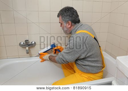 Worker Caulking Bath Tube And Tiles