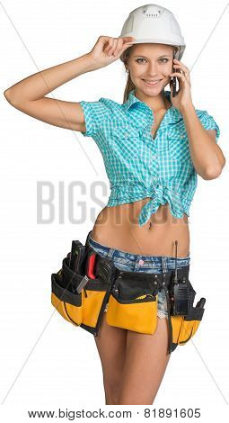 Woman in hard hat and tool belt calling on mobile phone