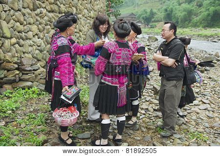 Women sell souvenirs to a tourist in Longji, China.