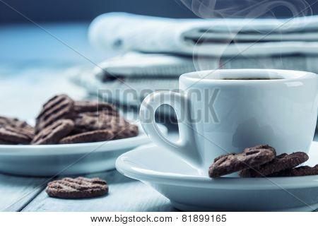 Cup of coffee , chocolate biscuits and the background newspaper.