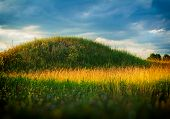 stock photo of steppes  - hill and grass spring evening clouds in the steppe   - JPG