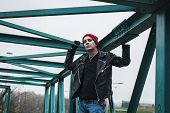stock photo of anarchists  - Punk guy with beanie standing on a bridge - JPG