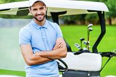 stock photo of ball cap  - Handsome young man keeping arms crossed and smiling while leaning at the golf cart while standing on golf course - JPG