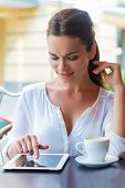 image of toothless smile  - Beautiful young woman working on digital tablet and smiling while sitting at the sidewalk cafe - JPG