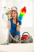 picture of kneeling  - A young housewife kneeling beside the vacuum cleaner with duster in hand satisfied with the good work cleaning up the house - JPG