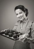 picture of chocolate muffin  - Smiling vintage woman holding a baking tray with chocolate home made muffins - JPG